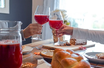 Hands clink wine glasses filled with a frothy red beverage, over a pie-laden table
