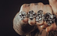 Threatening fist with metal rings and tattoos; credit: Photo by Clem Onojeghuo on Unsplash