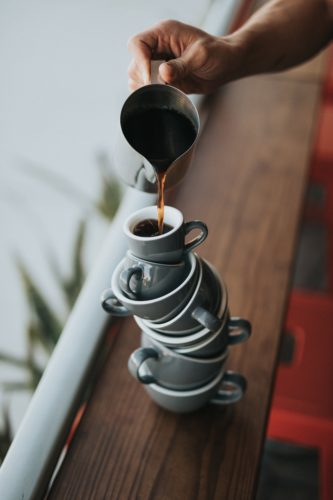 Emotional overload as a teetering stack of coffee cups; Photo by Nathan Dumlao on Unsplash