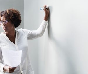 A teacher stands at a white board, poised to write. Her expression is earnest.